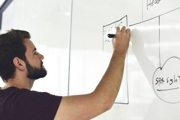 Mand der tegner på white board